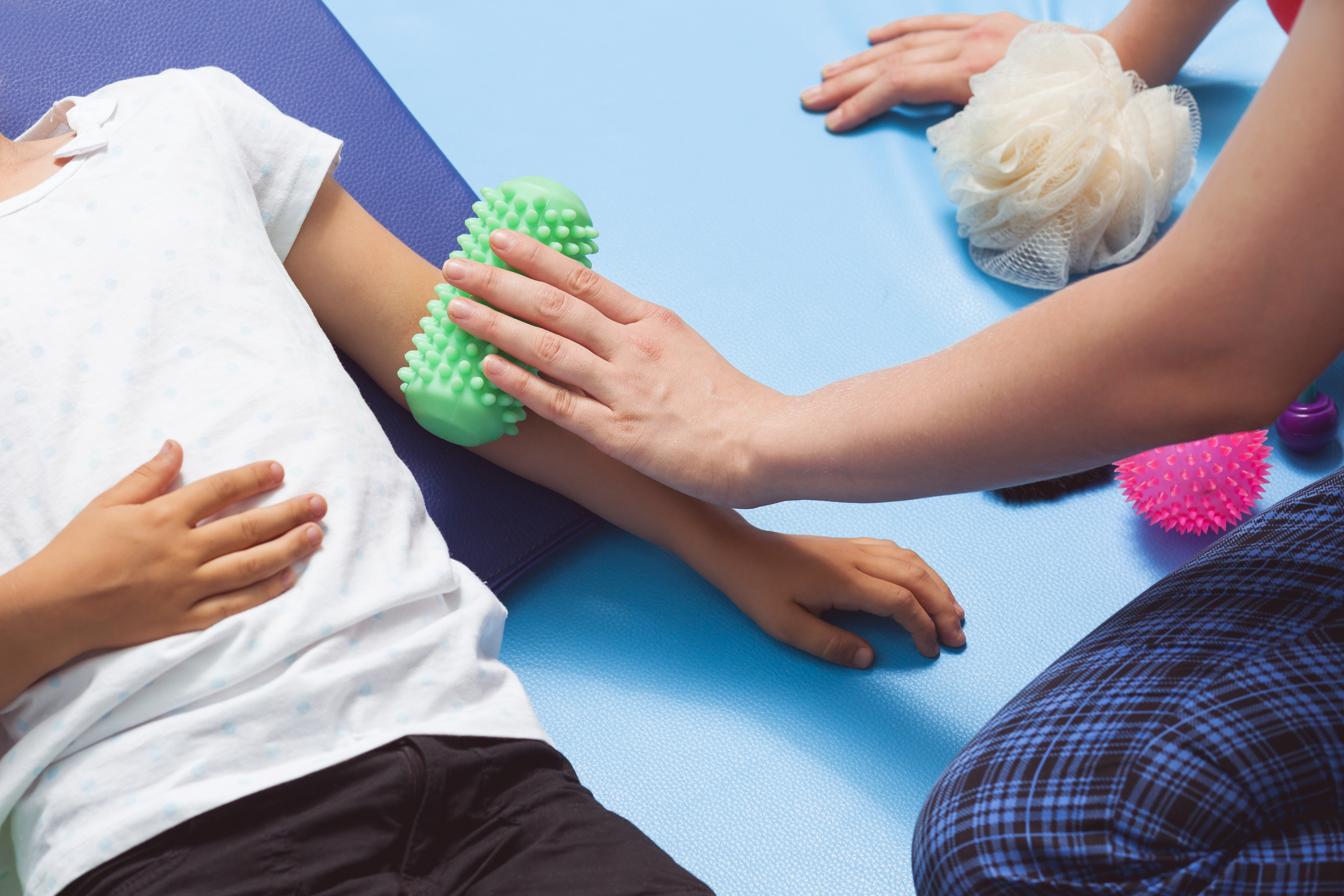 Therapist making a roll massage on young girl's arm